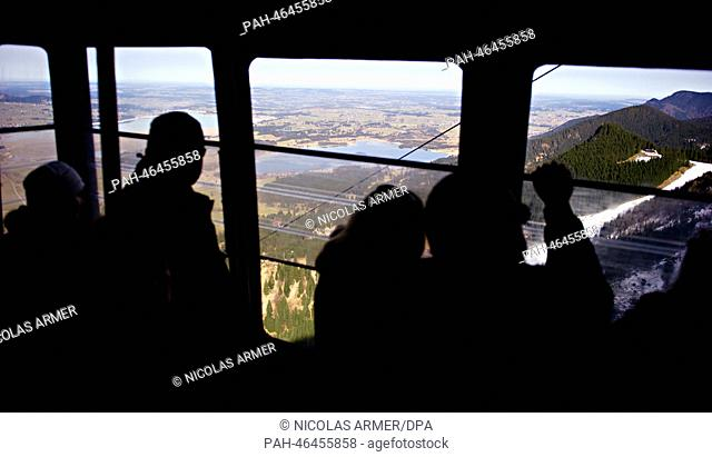 Passengers look at the landscape underneath them during a trip in a gondola onto Tegelberg mountain near Schwangau, Germany, 18 February 2014