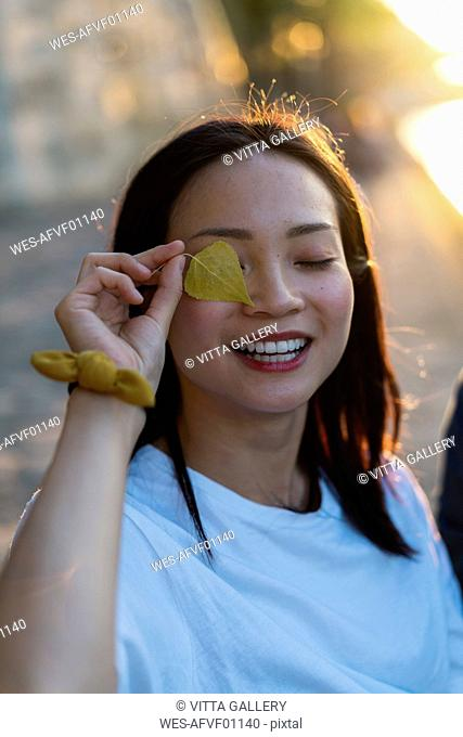 Portrait of happy young woman holding leaf in front of her eye