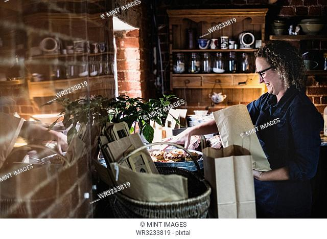 Smiling woman wearing glasses placing freshly baked pies in brown paper shopping bag