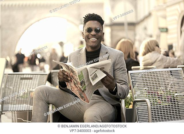 Young African man sitting on chair, reading newspaper, in Munich, Germany