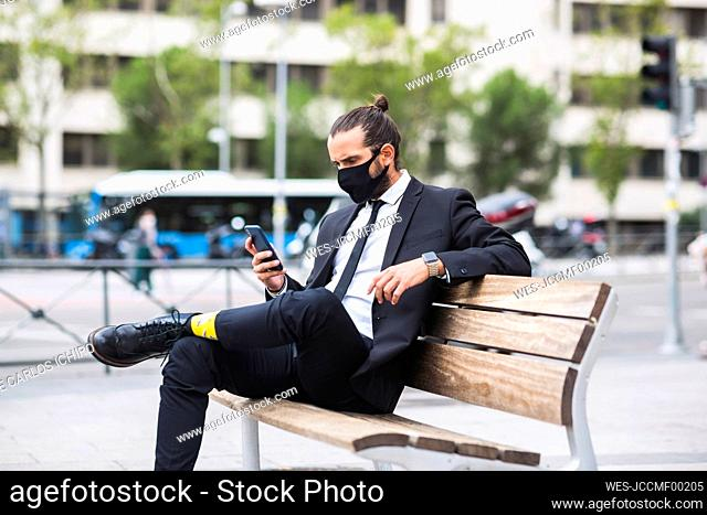 Businessman wearing protective face mask sitting on bench with smart phone in hand