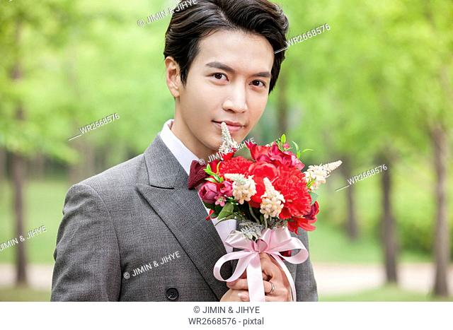 Portrait of young smiling groom with flowers outdoors