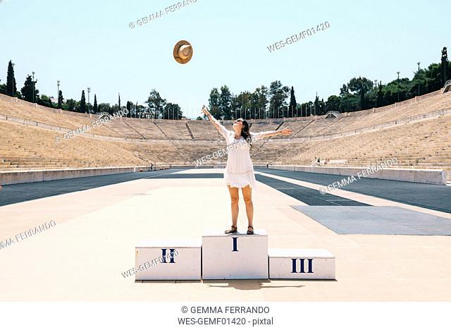 Greece, Athens, woman on the podium celebrating in the Panathenaic Stadium