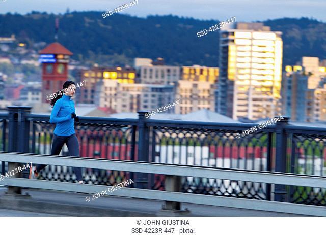 Woman running along bridge
