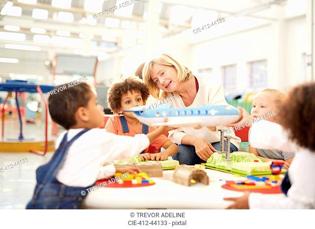 Teacher showing toy airplane to kids in science center