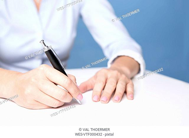 Woman signing document on the table