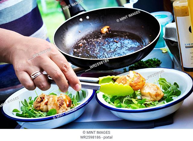 Woman standing at a camping stove, preparing two plates with fried scallops and fresh herbs