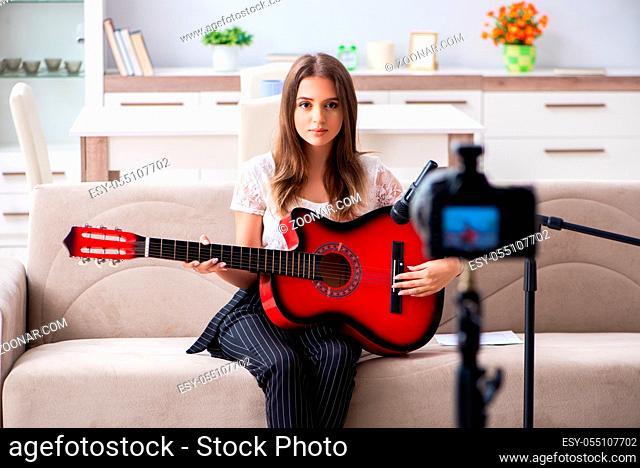 Female beautiful blogger playing guitar