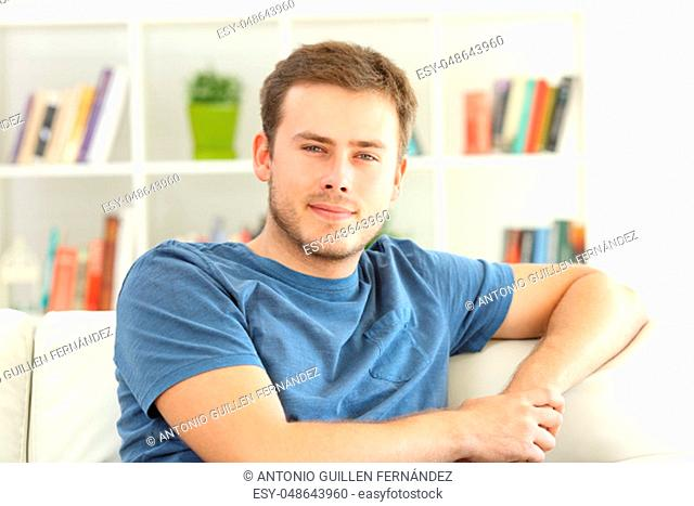 Portrait of a relaxed man looking at you sitting on a sofa at home