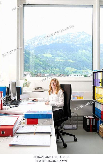 Caucasian businesswoman smiling at office desk