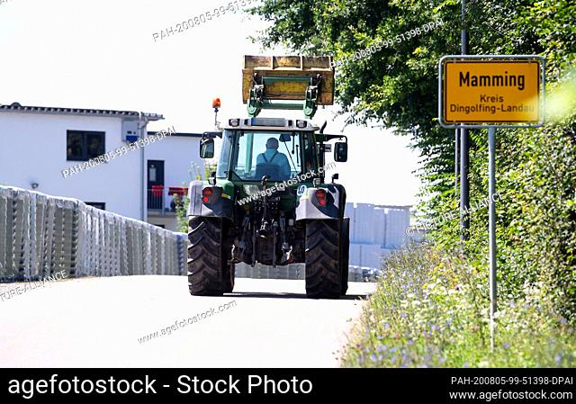 05 August 2020, Mamming: A farmer drives with his tractor along the town sign of Mamming and a cannery. The number of corona infected people in Mamming...