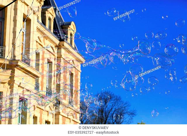 Soap bubbles floating in a blue sky in the city
