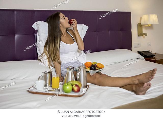 Young woman chilling on bed with tray of fruit and juice eating fresh apple in hotel room