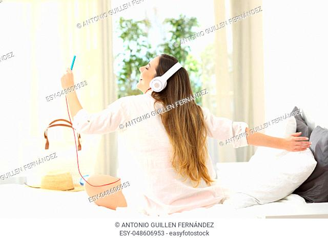 Back view portrait of a happy girl enjoying vacations listening to music on a bed in an hotel room