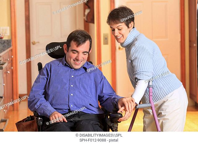 Woman with Cerebral Palsy using crutches and helping her husband with Cerebral Palsy use his motorized wheelchair
