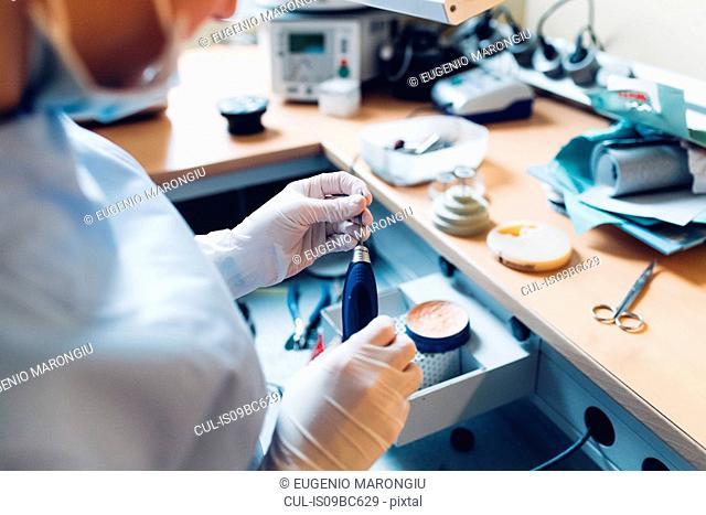 Female dentist handling dentistry equipment in dentist office, mid section