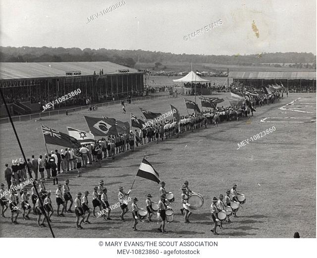 Dutch boy scouts on a parade ground with flags of various nations and musical instruments