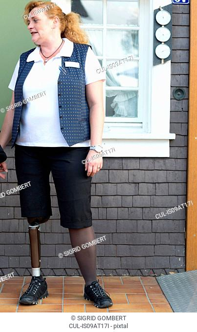 Mid adult woman with prosthetic leg, standing outside