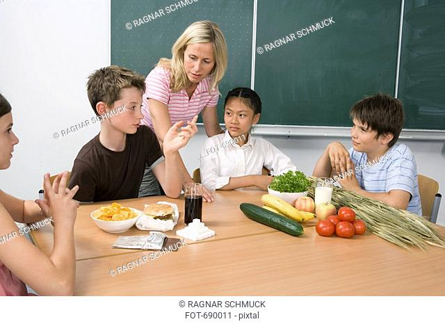 A teacher and four students learning about nutrition