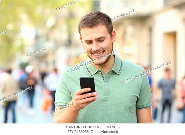 Front view portrait of a man walking and using a smart phone on the street