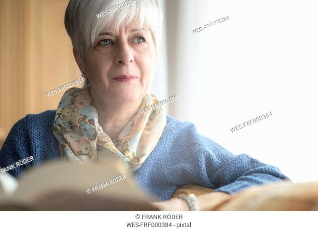 Portrait of senior woman with a book