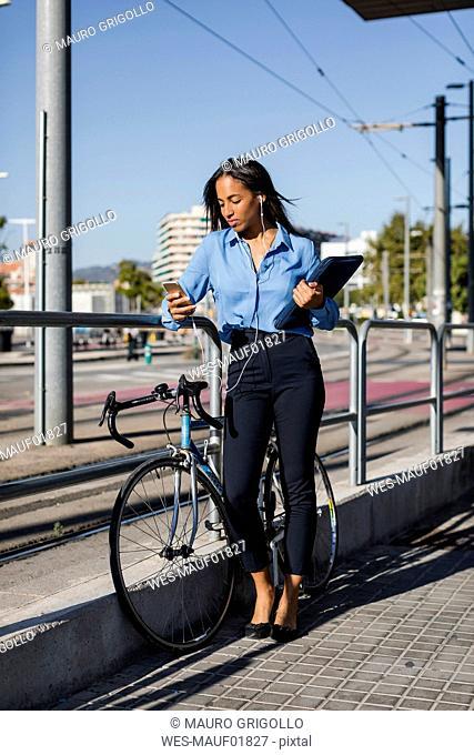 Businesswoman using smartphone, laptop bag