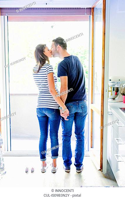 Rear view of couple by baby shoes kissing