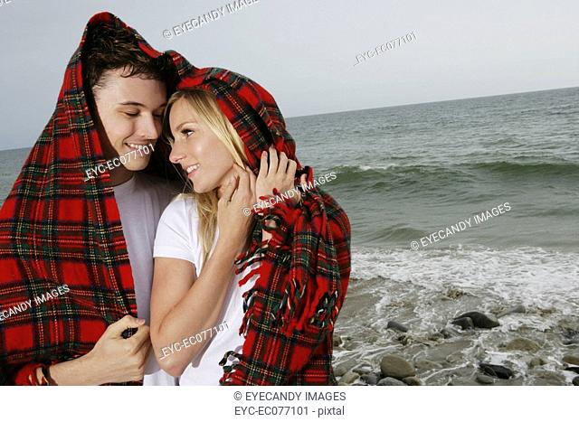Portrait of young couple with blanket standing on beach