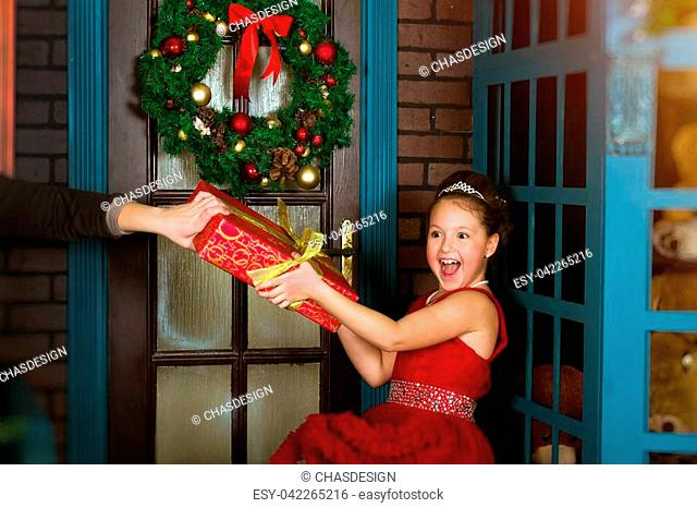 Little winter Princess in red dress accepts a Christmas gift from hands of giver. New year and Christmas celebration in enchanting holiday interior with...