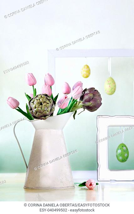 Pitcher with pink tulips and artichokes with white frames and Easter eggs in the background. Still life with spring mood in pastel colors