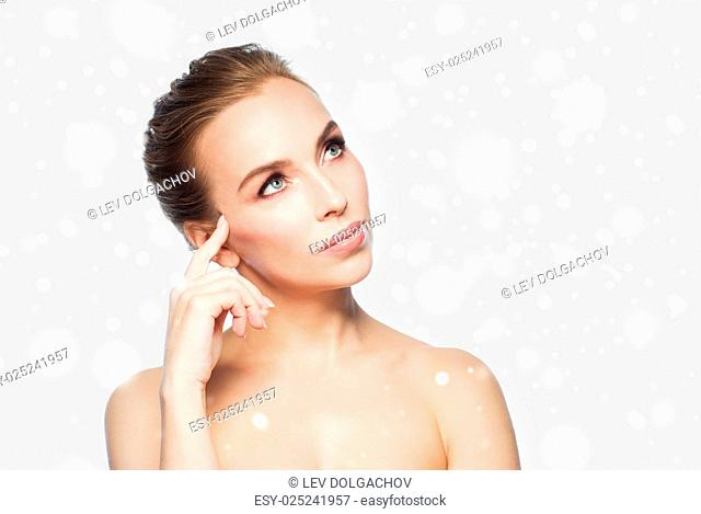 beauty, people, winter and health concept - beautiful young woman touching her face over gray background and snow