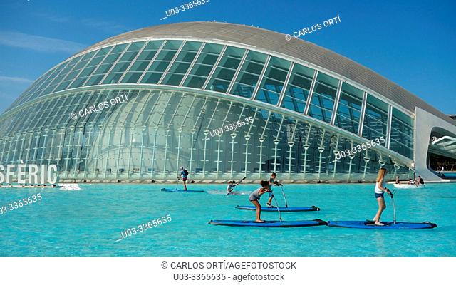Tourists sailing in a small lake in front of the Hemisferic building, City of Arts and Sciences Complex. Spanish city of Valencia, Europe