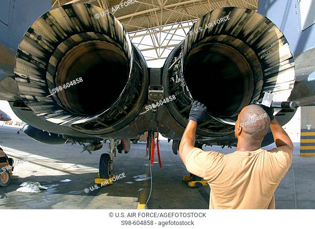 A maintainer with the 379th Expeditionary Aircraft Maintenance Squadron inspects the engine of an F-15E Strike Eagle at a forward-deployed location in Southwest...