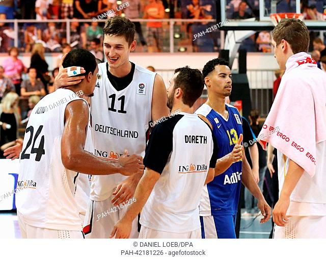 Germany's Tibor Pleiss (2-L) celebrates with Alex King (L) and Bastian Doreth (C) after winning the international basketball match between Germany and Sweden...
