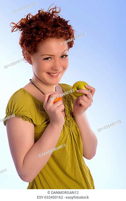 caucasian girl with positive natural smile making choice between two types of fruits isolated
