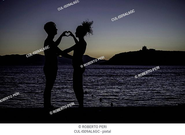 Couple making heart shape with hands by sea, silhouette