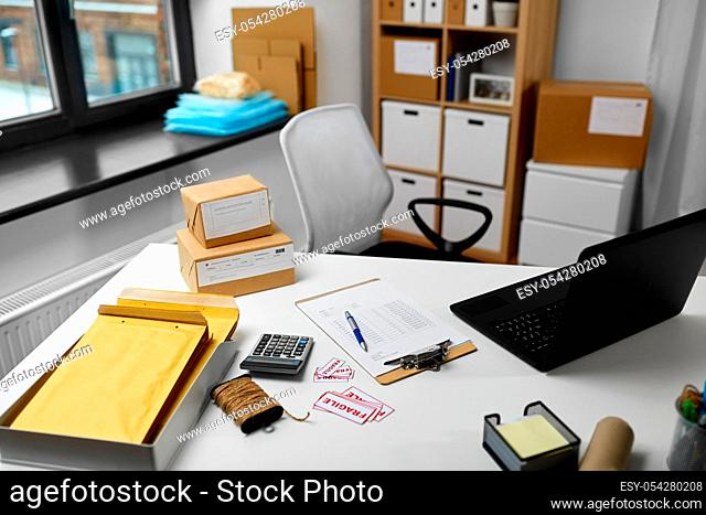 laptop and parcels on table at post office