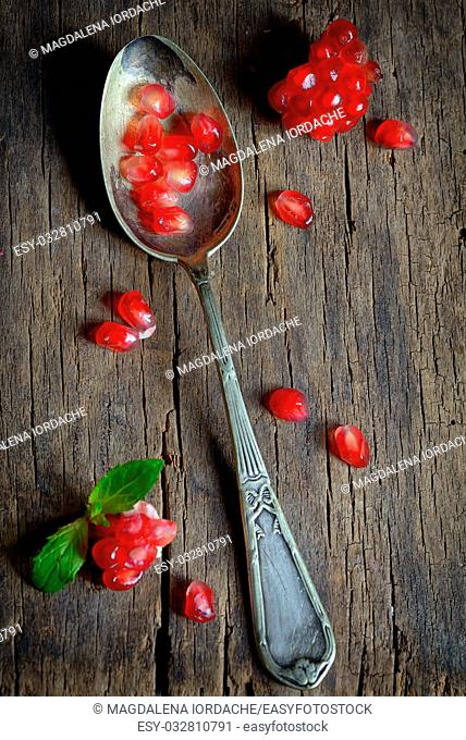 Ripe pomegranate and spoon on wooden table