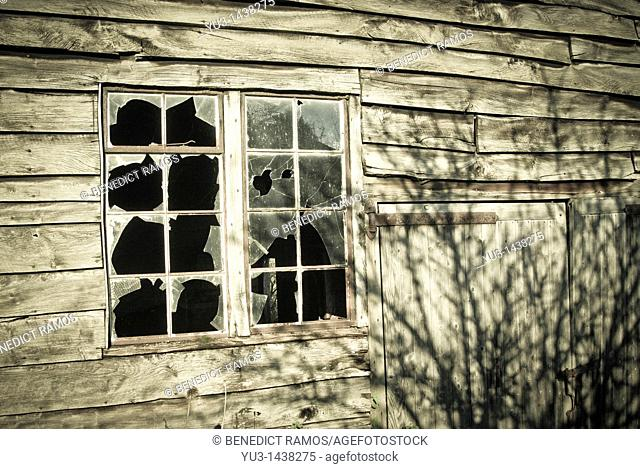 Broken window panes on wooden outbuilding