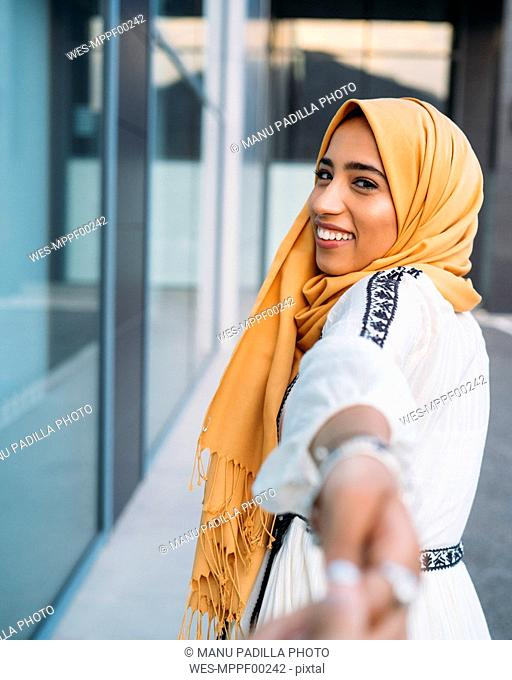 Young muslim woman smiling and taking hand of a man wearing hijab