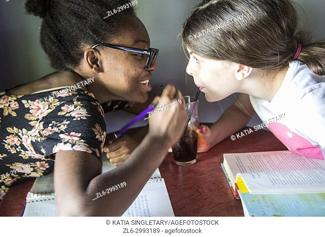 African American pre Teen/ teen with glasses sipping soda in the same glass than a caucasian pre teen/teen. They are both drinking from a straw the same soda