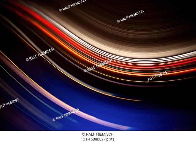Full frame abstract image of colorful light trails against black background