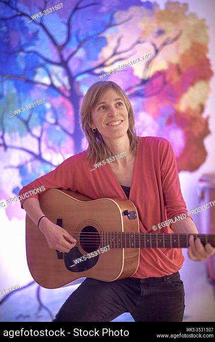 creative woman playing acoustic guitar