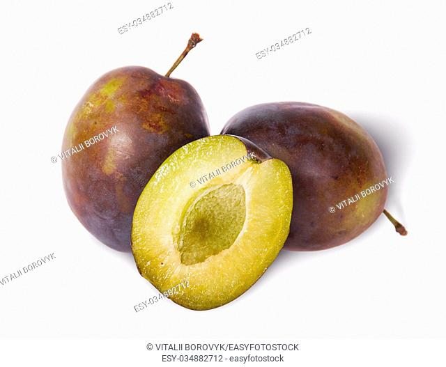 Two violet plums and half stand isolated on white background