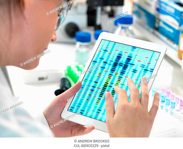 Female scientist examining DNA sequence results on digital tablet in laboratory