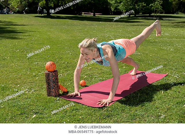 Woman in training clothing with gymnastics balls on pink mat in the park