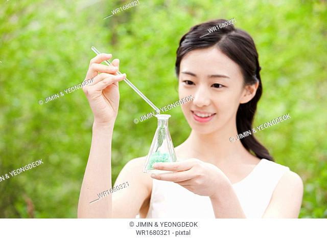 a woman holding a chemistry bottle in the nature