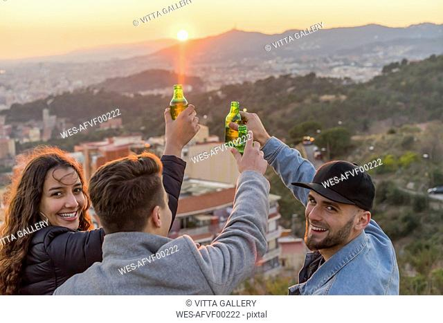Spain, Barcelona, three happy friends with beer bottles on a hill overlooking the city at sunset