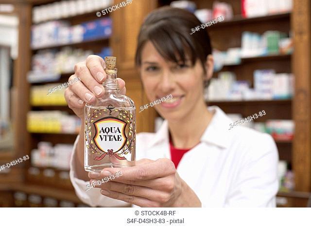 Female pharmacist holding a bottle of Aqua Vitae aquavit, water of life at camera