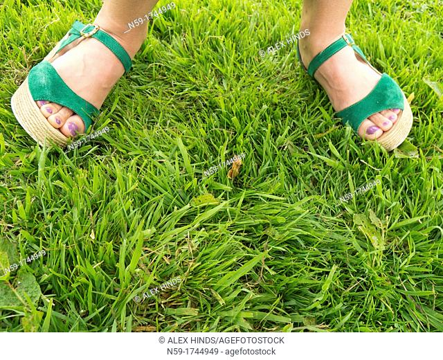 Woman's feet in green sandals on grass